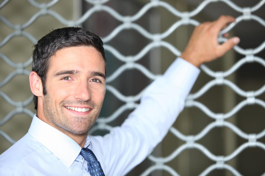 A man standing with a fence