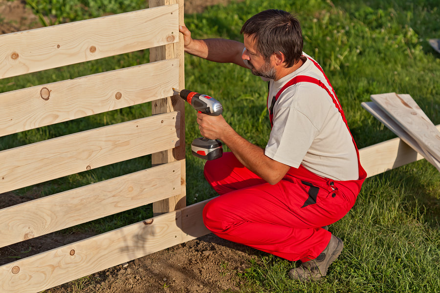A man building a wood fence